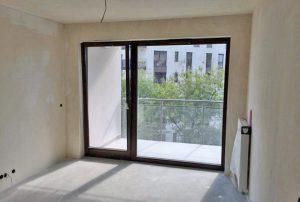widok na salon i balkon w mieszkaniu do sprzedaży w Warszawie